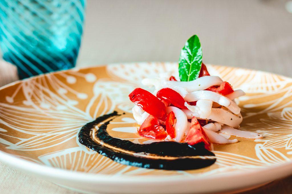 Julienne di seppia con pomodorini e salsa al nero di seppia